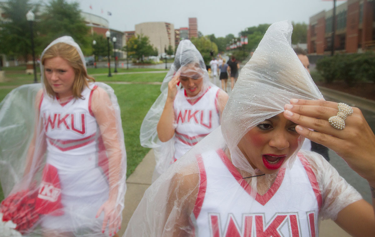 Looking to escape from the rain, Louisville senior Jasmine Taylor walks down Avenue of Champions to a tent on South Lawn at Western Kentucky University Saturday. The rain before WKU's first football game of the season caused Topper Walk, a pre game tradition in which players, cheerleaders and marching band members walk to the stadium, to be cancelled.