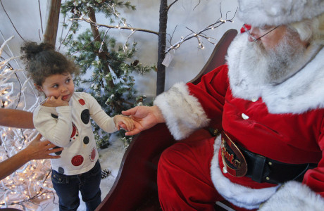 """Kinleigh Neal, a 3-year-old from Bowling Green is encouraged to visit Santa Saturday at Deemer's Flowers. Murray McCandless of Elizabethtown played Santa at the store's Christmas open house. """"I looked in the mirror one day, said I'm fat and have a white beard, what am I going to do?"""" said McCandles, who is in his fifth year playing Santa."""
