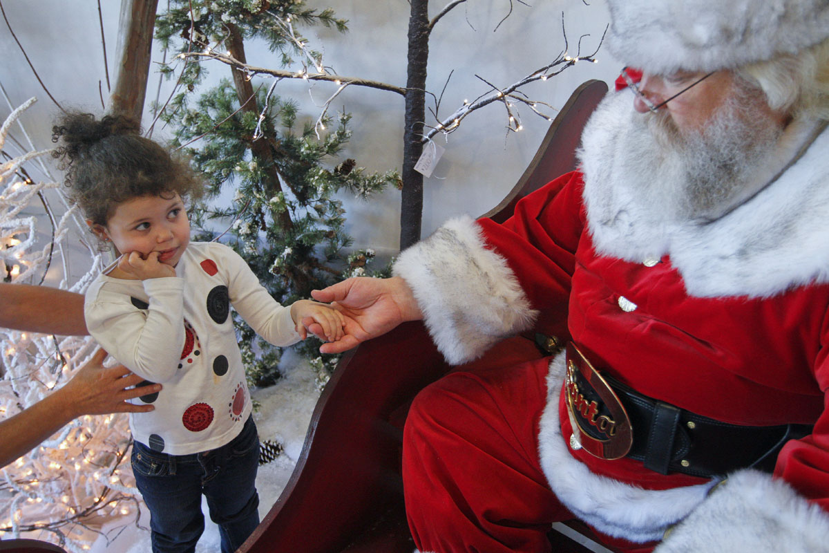 "Kinleigh Neal, a 3-year-old from Bowling Green is encouraged to visit Santa Saturday at Deemer's Flowers. Murray McCandless of Elizabethtown played Santa at the store's Christmas open house. ""I looked in the mirror one day, said I'm fat and have a white beard, what am I going to do?"" said McCandles, who is in his fifth year playing Santa."