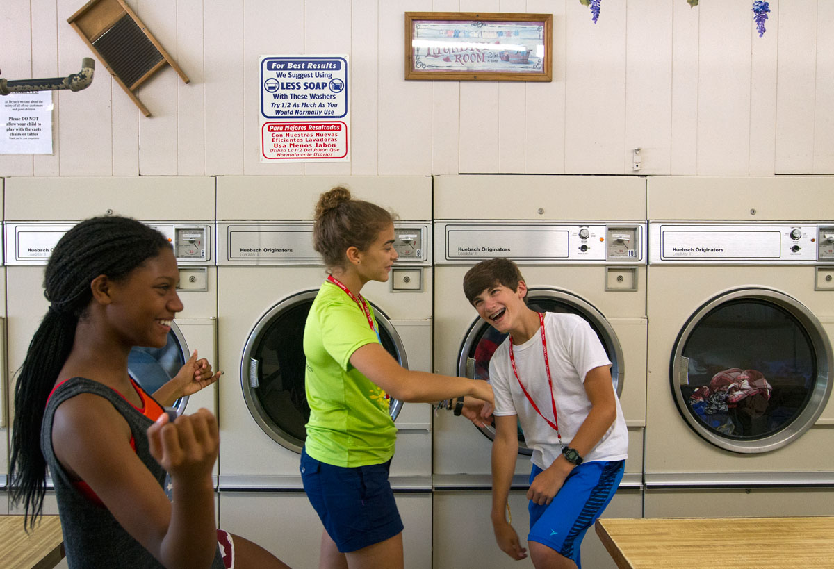 VAMPY campers Jocelyn Martin (from left) of Russell and Maya Abul-Khoudoud of Ashland teach a dance to Grant Coorssen of Louisville while waiting for their clothes to dry at Bryce's Bypass Laundromat Sunday, July 10.