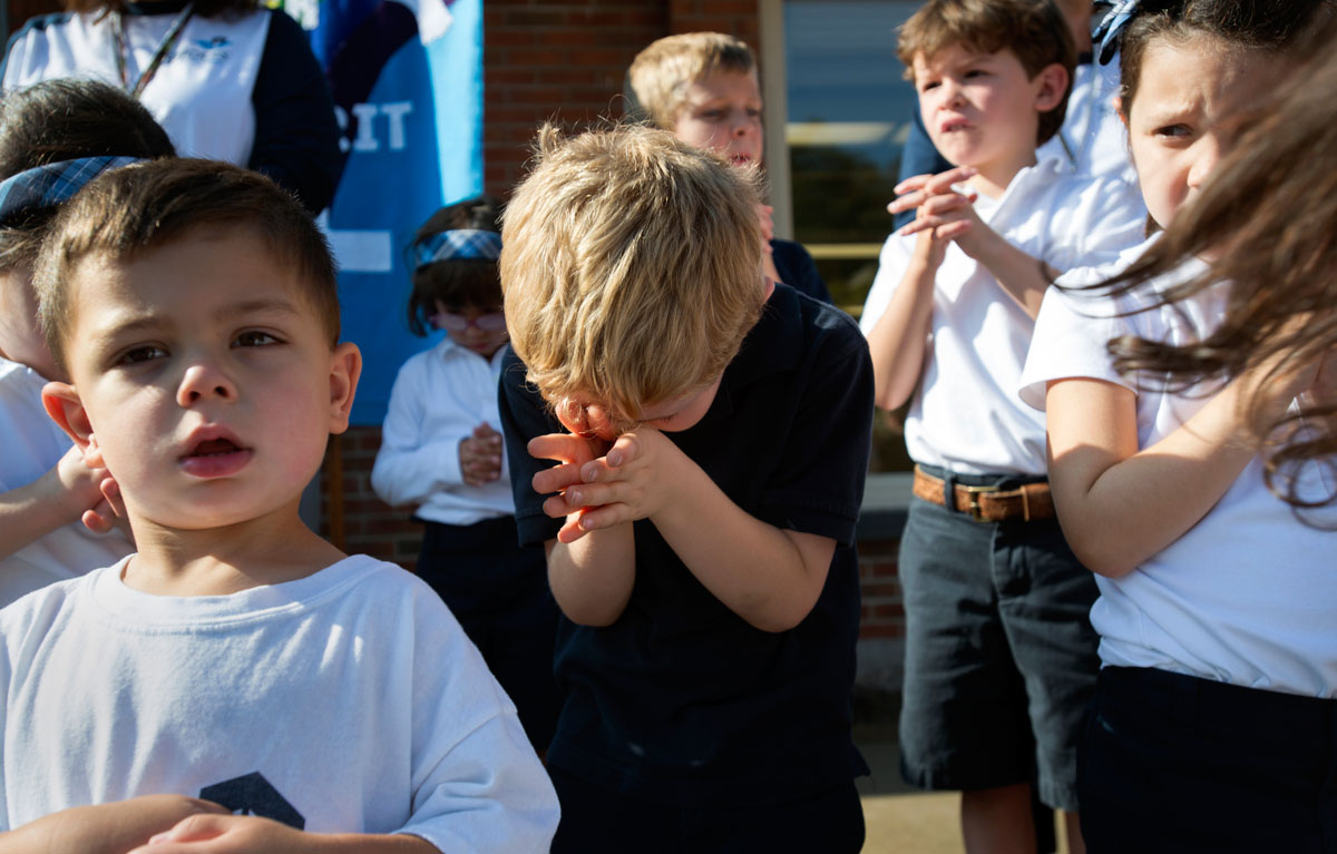 Kindergartner Jackson Hickey takes a prayerful stance while Father Bob Ring gives a blessing over the new Early Learning Center at St. Louis School in Pittsford Sept. 20.