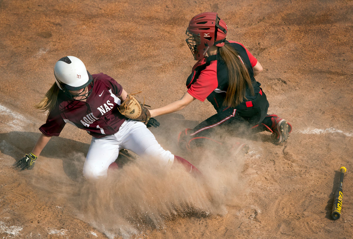 Megan Hildebrand slides safely into home plate to score in the fifth inning of Aquinas Institute's 5-3 loss to Geneva May 29 in the Section Five Class A2 championship game at the State University of New York at Brockport.