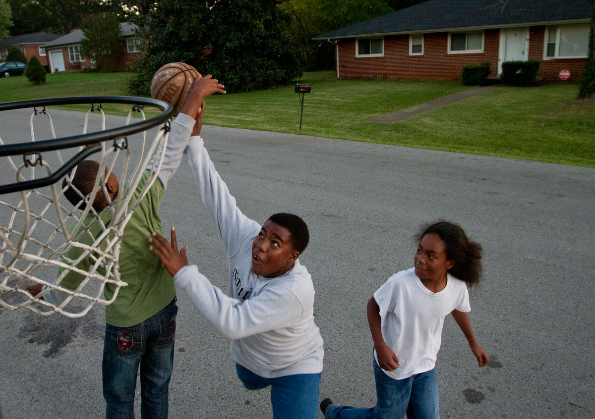 Eleven-year-old Liorell Gray tries to dunk over his cousin 13-year-old Thomas Maxey while playing basketball with their soon-to-be cousin, 12-year-old Meikiel Ya Monday, Oct. 8. The three were playing outside of Gray's home on Gatewood Drive in Bowling Green.
