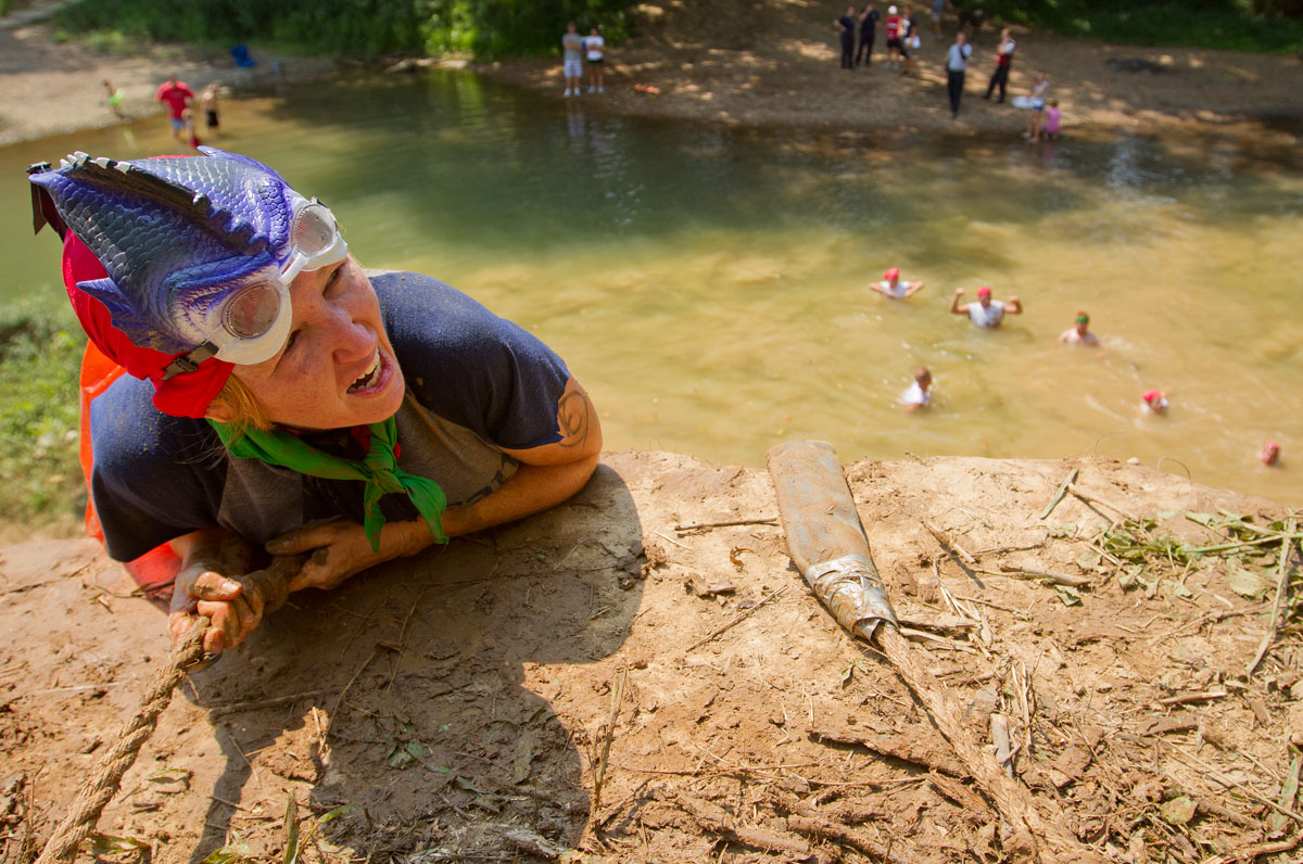 A competitor climbs a cliff during the  BG Gauntlet, the first annual mud run held to benefit the Family Enrichment Center August 25 at Phil Moore Park in Bowling Green.