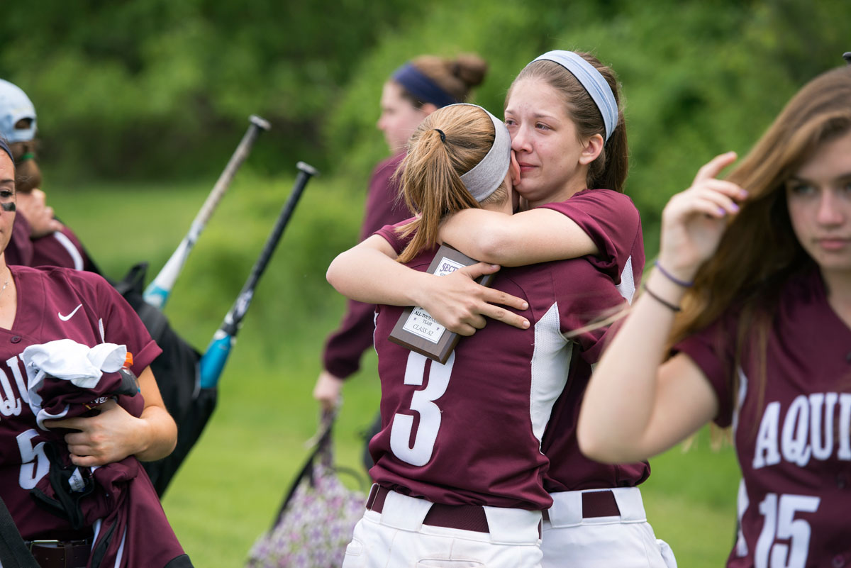 Sam Ashman hugs Sarah Gensler (3) after Aquinas' 5-3 loss in the Section Five Class A2 championship game. Ashman was named to the all-tournament team.