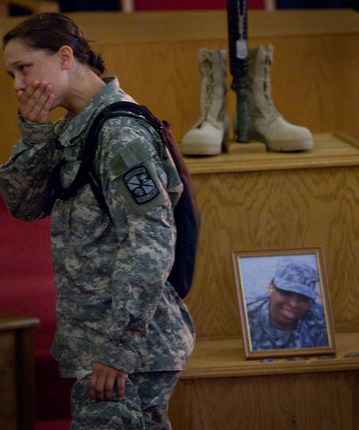 After a memorial service for cadet Carmela Kirkland, cadet Hannah Metheny passes by a photo of the deceased cadet and a display of her combat boots, rifle and kevlar helmet.
