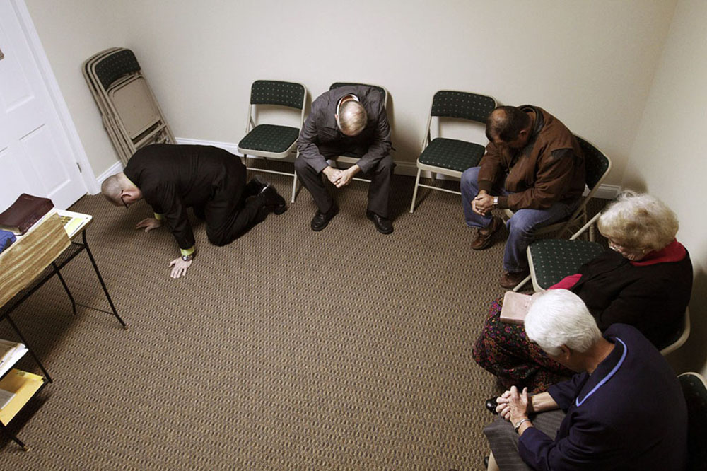 Before a revival-week service at White Oak Baptist Church, Reggie prays with church members in the church basement. They prayed for the success of the service as well as church members in need of prayer.