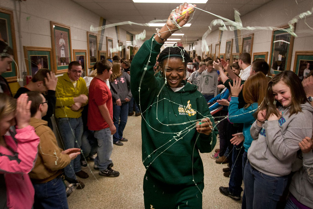 Leading her teammates to the bus bound for State, senior Shay Walker sprays silly string on students lining the hallways of Greenbrier East High School in Lewisburg, West Virginia, Wednesday.