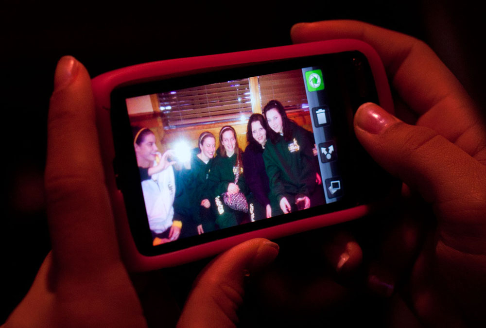 Waiting for a table at Outback Steakhouse in Charleston the night before playing in the state tournament, freshman Chaunte McDowell reviews a picture she took of her teammates. The team often goes out to eat together, especially after winning close games.
