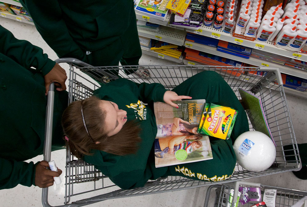 Shopping for supplies to make a banner, freshman Elizabeth Romeo rides in a shopping cart and reads a magazine Tuesday night. After shopping together at Walmart, members of the team went to senior Shay Walker's house to decorate the banner.