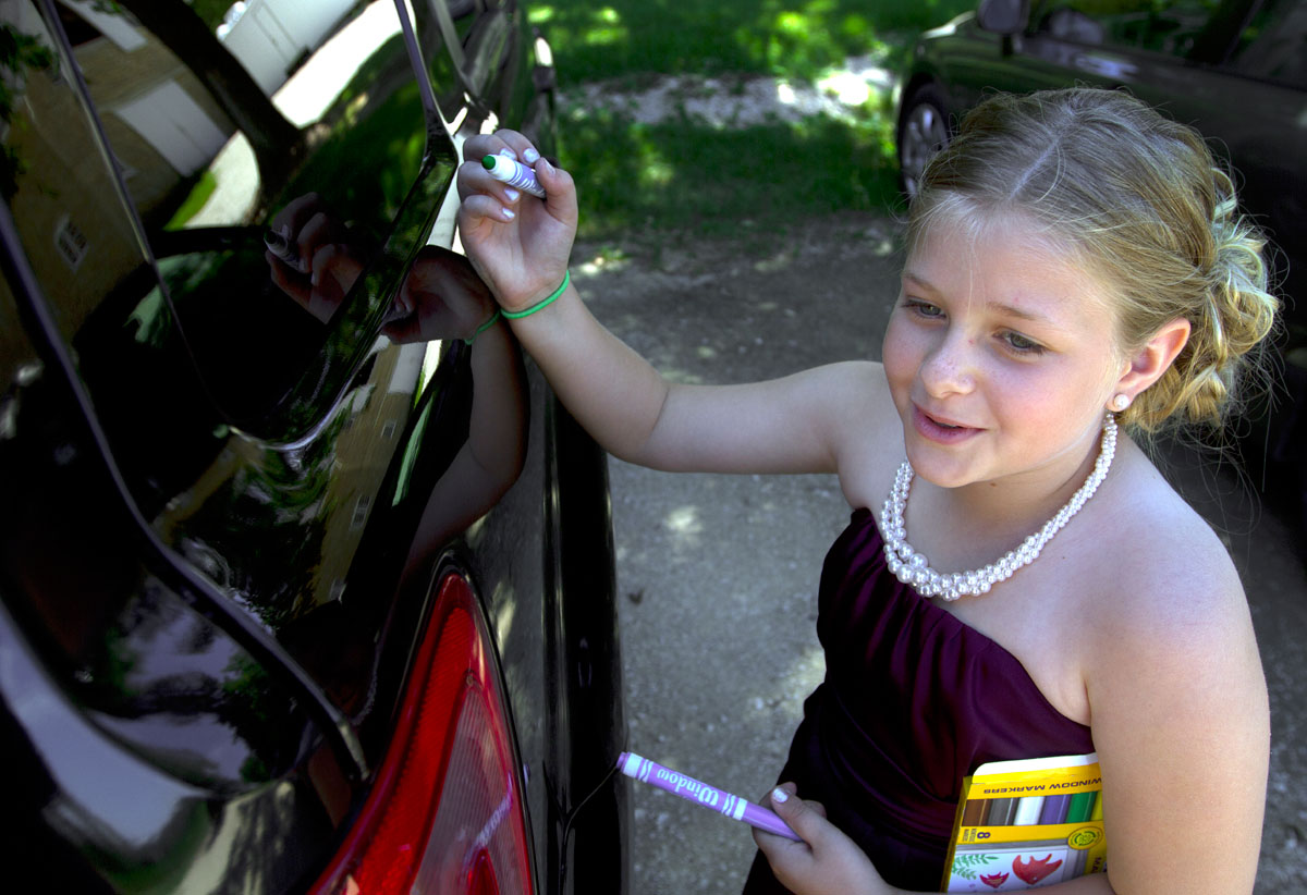 Kari's youngest sister, Miah, a junior bridesmaid, draws on Brandon's car before the ceremony.
