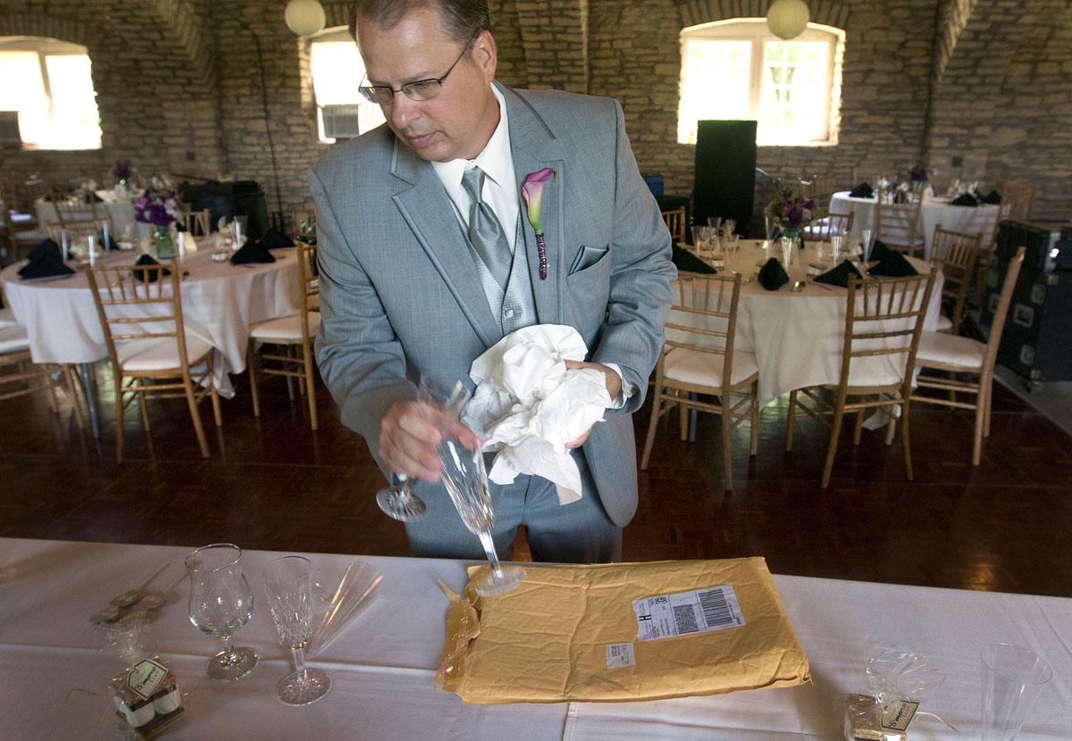 Kari's dad, Dean, places champagne glasses at the head table before the ceremony.