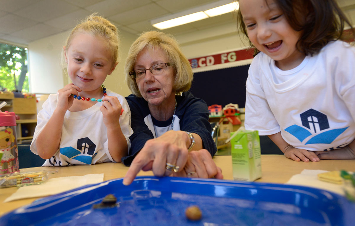 Kathy Conezio watches slugs with students during snack time in her 3-year-old preschool class at St. Louis School in Pittsford. Conezio has been a science consultant for Sesame Street since the late 1990s and began teaching at St. Louis School this year.