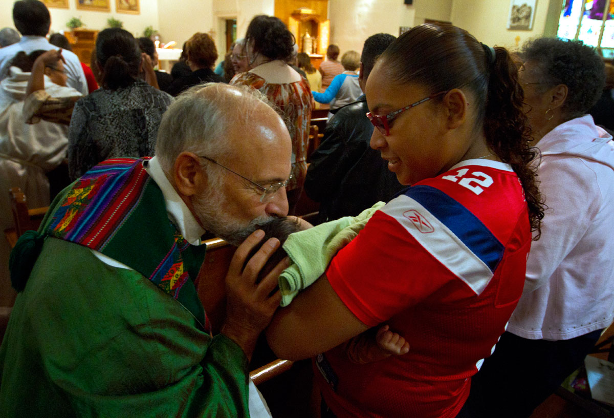 Father Tony Mugavero kisses a child during the sign of the peace at a Mass to celebrate Hispanic Heritage Month Sept. 22 at Holy Apostles Church in Rochester.