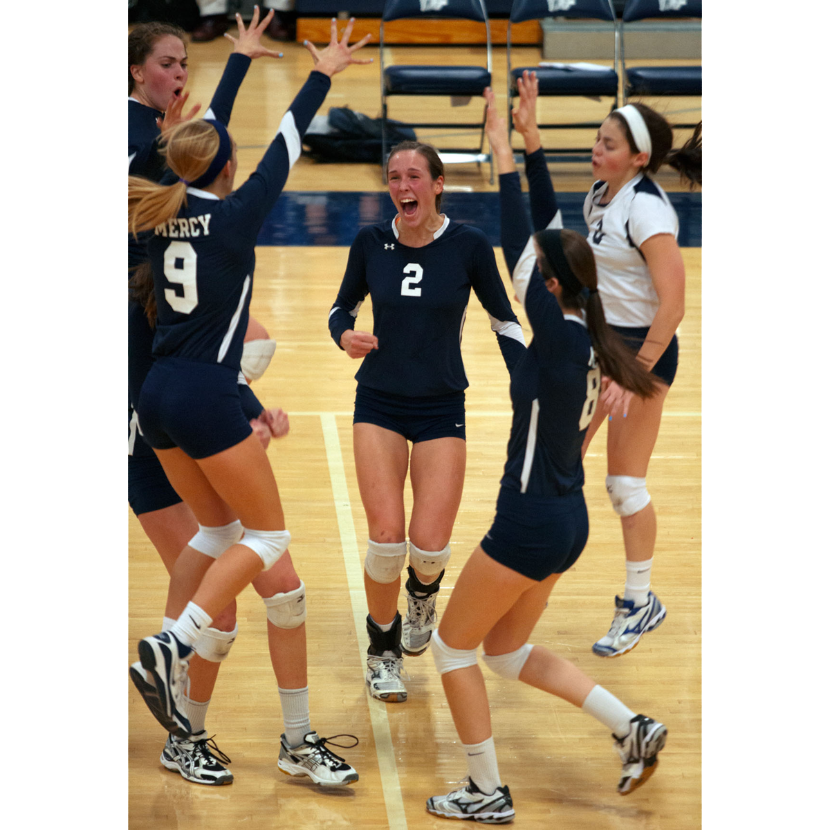 Sophomore Hannah Cannon (2) celebrates with teammates between points Nov. 1 at Gates Chili High School. Mercy defeated Penfield in five sets to win the sectional title.
