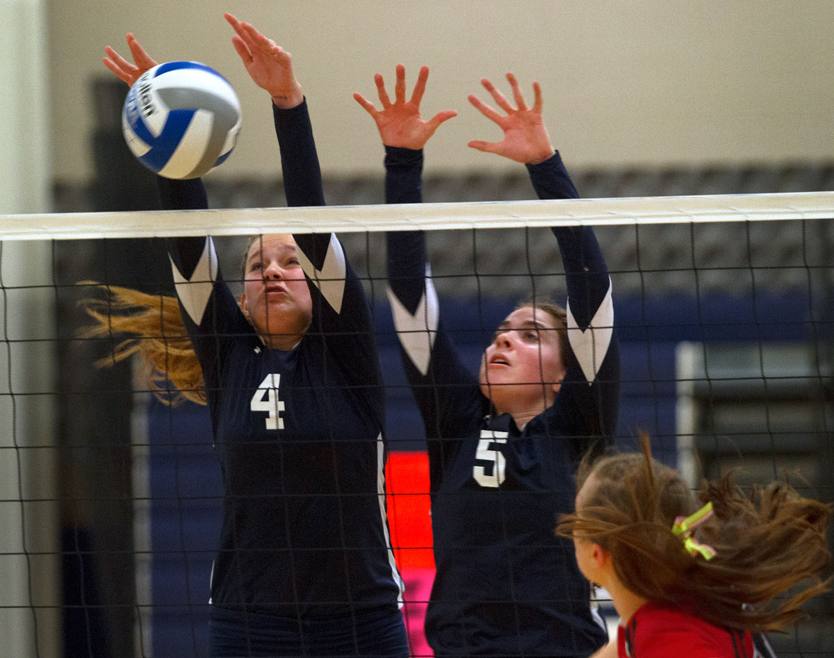 Sophomores Megan Hobler (4) and Caroline Crilly (5) block a hit from Penfield Nov. 1 at Gates Chili High School. Mercy defeated Penfield in five sets to win the sectional title.