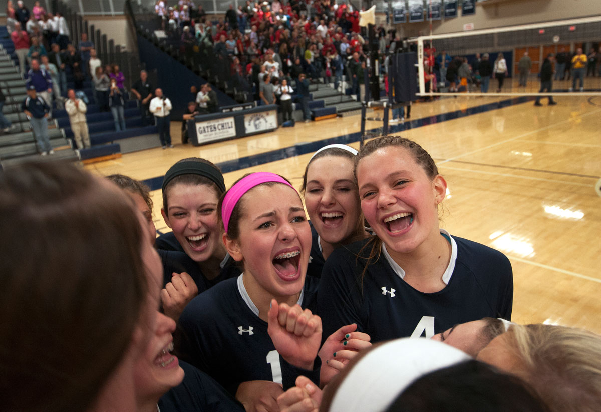 Members of Mercy's volleyball team celebrate after defeating Penfield after five sets to claim the sectional title Nov. 1 at Gates Chili High School.