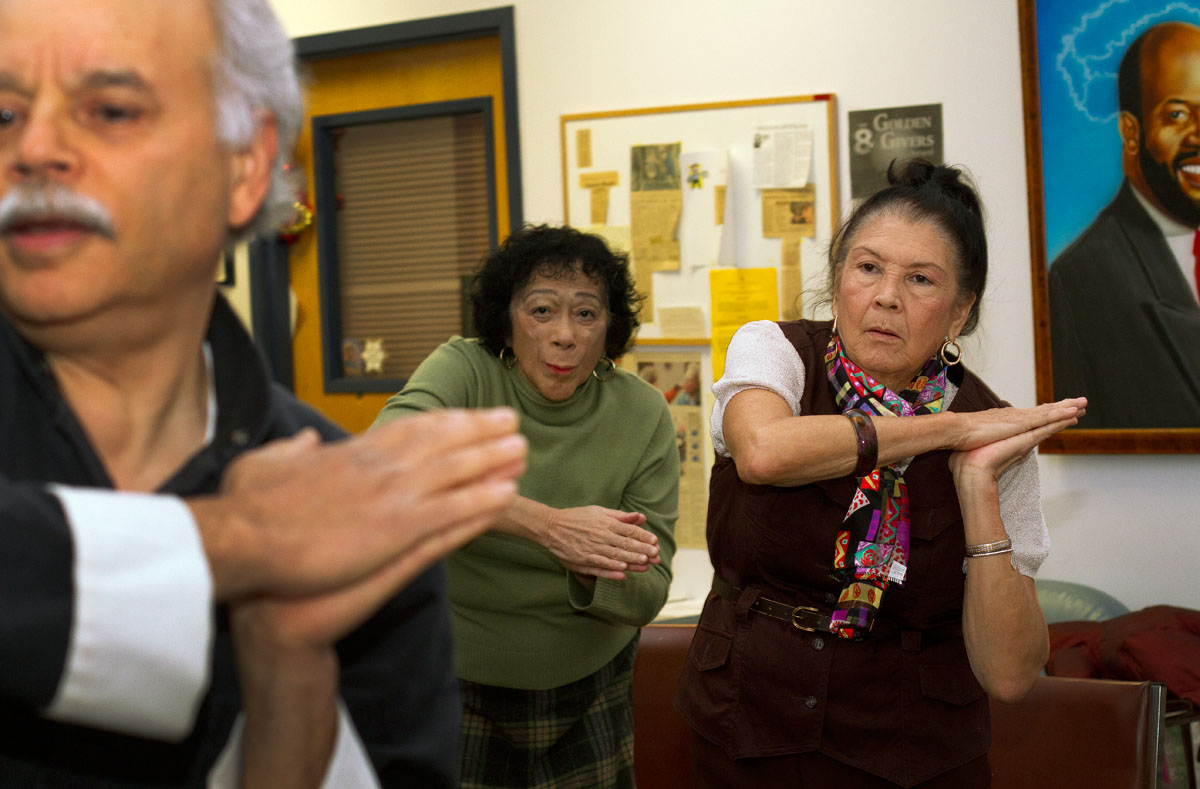 Bertha Bu Melian (right) and Aliza Gutierrez learn taiji from Carmelo Ramos during a conference for caregivers of Alzheimer's patients. Taiji can slow the progression of Alzheimer's disease, Ramos said.