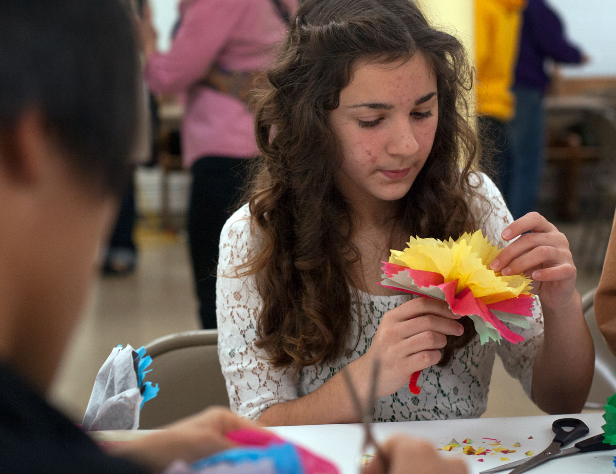 Katharina Nieves makes a flower out of tissue paper and a pipe cleaner during the Day of the Dead celebration.  Students from York Central School volunteered at a variety of craft tables at the celebration after learning about the tradition in their Spanish class.