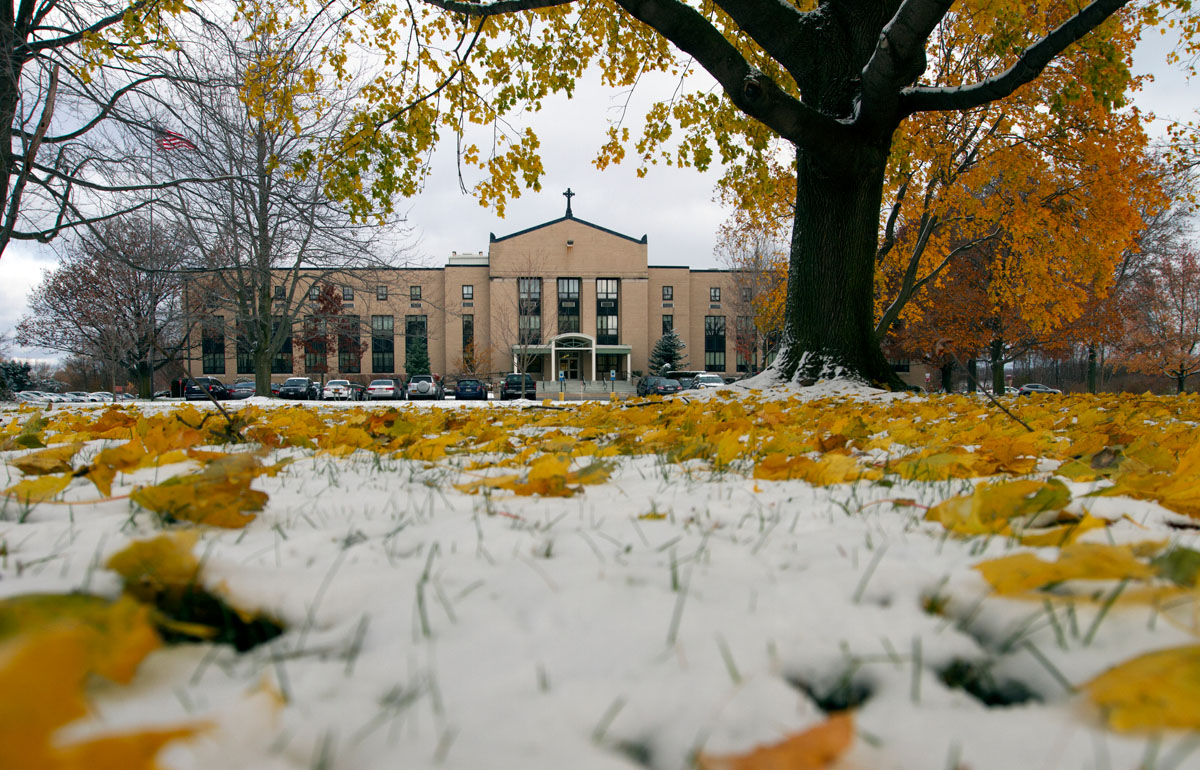 Snow and leaves cover the lawn outside the diocesan Pastoral Center on the day of the first snowfall of winter in Gates.