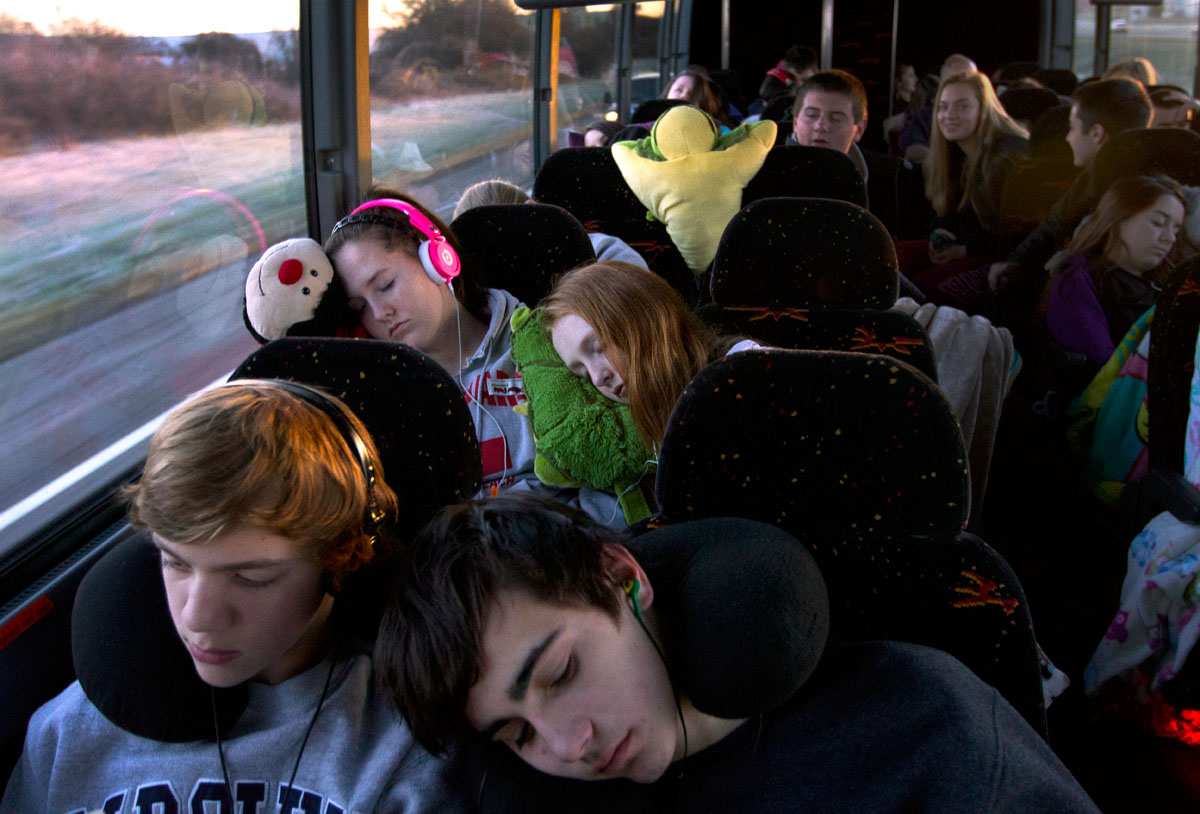 Riding on bus three to the National Catholic Youth Conference Nov. 20, 14-year-old Mary Panepento rests her head on her 15-year-old sister, Morgan Panepento's shoulder while Cooper Pievoni, 14, reads and Trevor Gross, 14, sleeps. All four are from St. Maximillian Kolbe Church in Ontario.