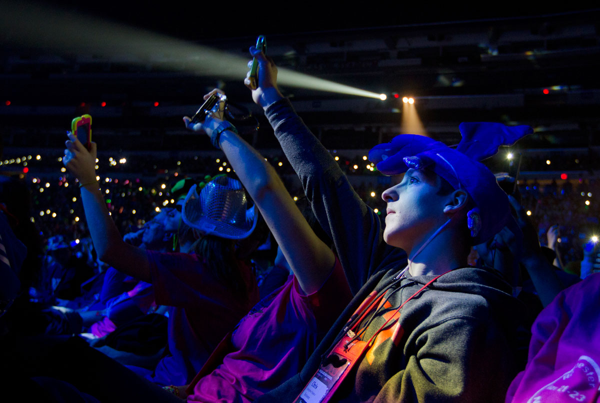 Chris Franco waves his cell phone in the air to give off light as the crowd was encouraged to do by Israel Houghton, the first musician to perform during the opening ceremony of the National Catholic Youth Conference Nov. 21 at Lucas Oil Stadium in Indianapolis.