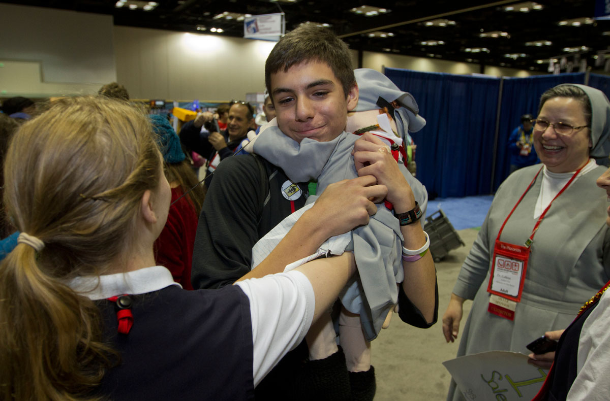 "Tyler Ray, 14, from St. Rita Church in Webster hugs Sister Marianette before hugging her handler, Sister Kelly Schuster, who is based out of New Jersey with the Salesians of Don Bosco. Ray was walking around NCYC with a sign that read ""Free Hugs."""