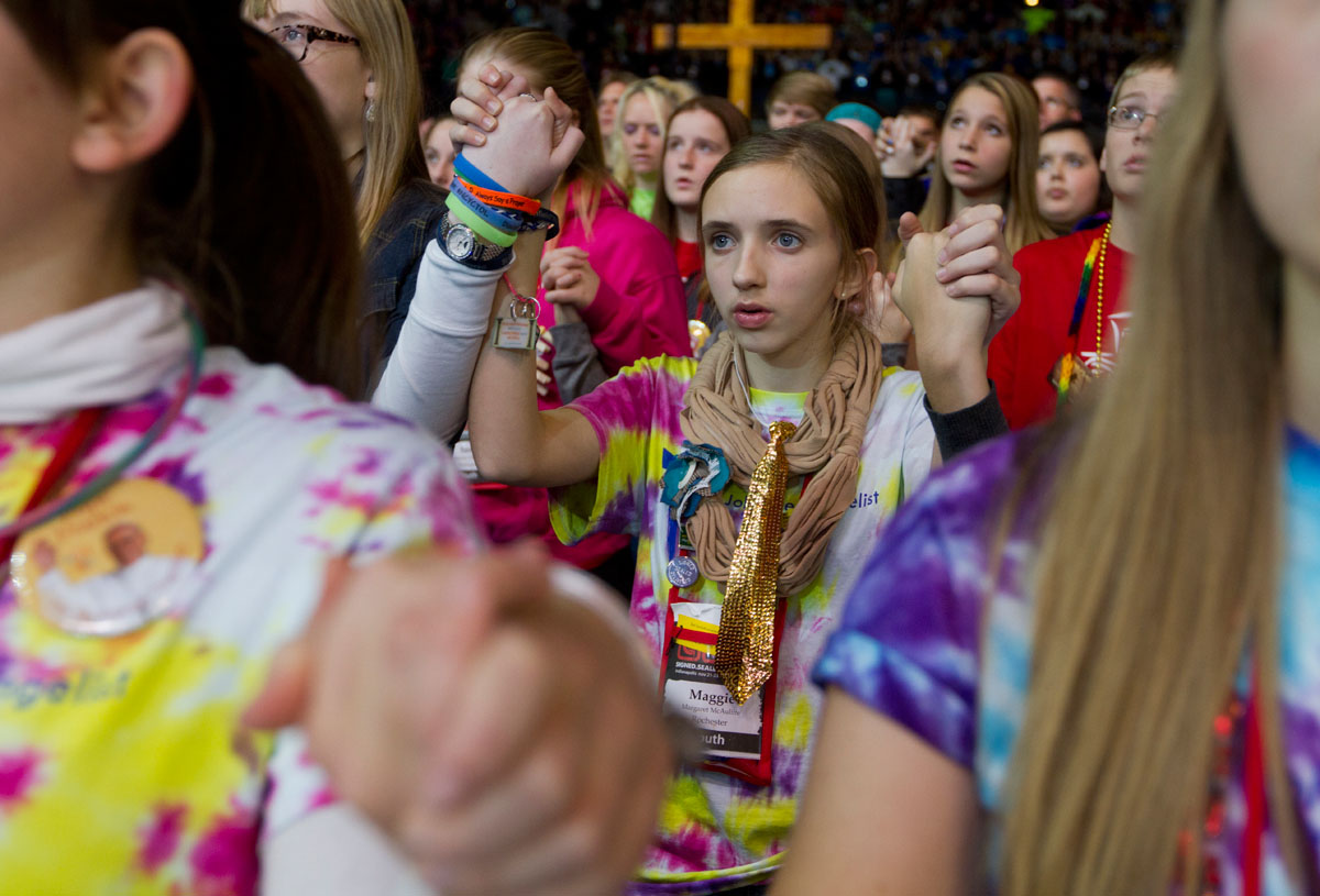 Maggie McAuliffe holds hands with other pilgrims from St. John the Evangelist in Spencerport while saying the Our Father during the closing Mass Saturday.