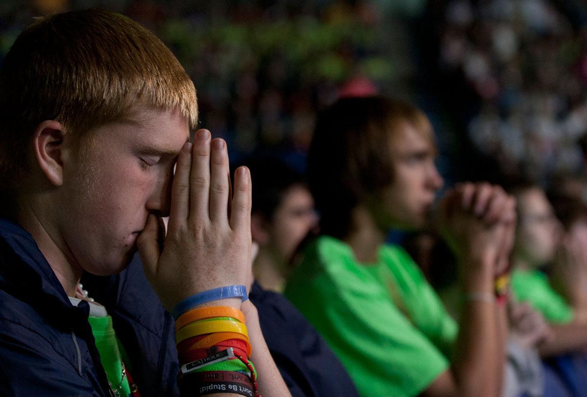 Dan Raftis, 15 from St. Patrick Church in Owego prays after receiving communion during the closing Mass Saturday.