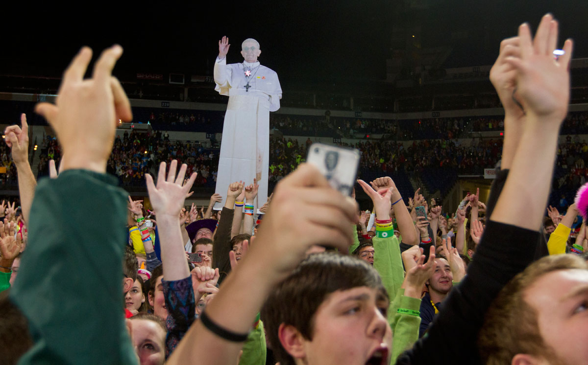 Pilgrims rush the stage after the closing Mass Saturday.