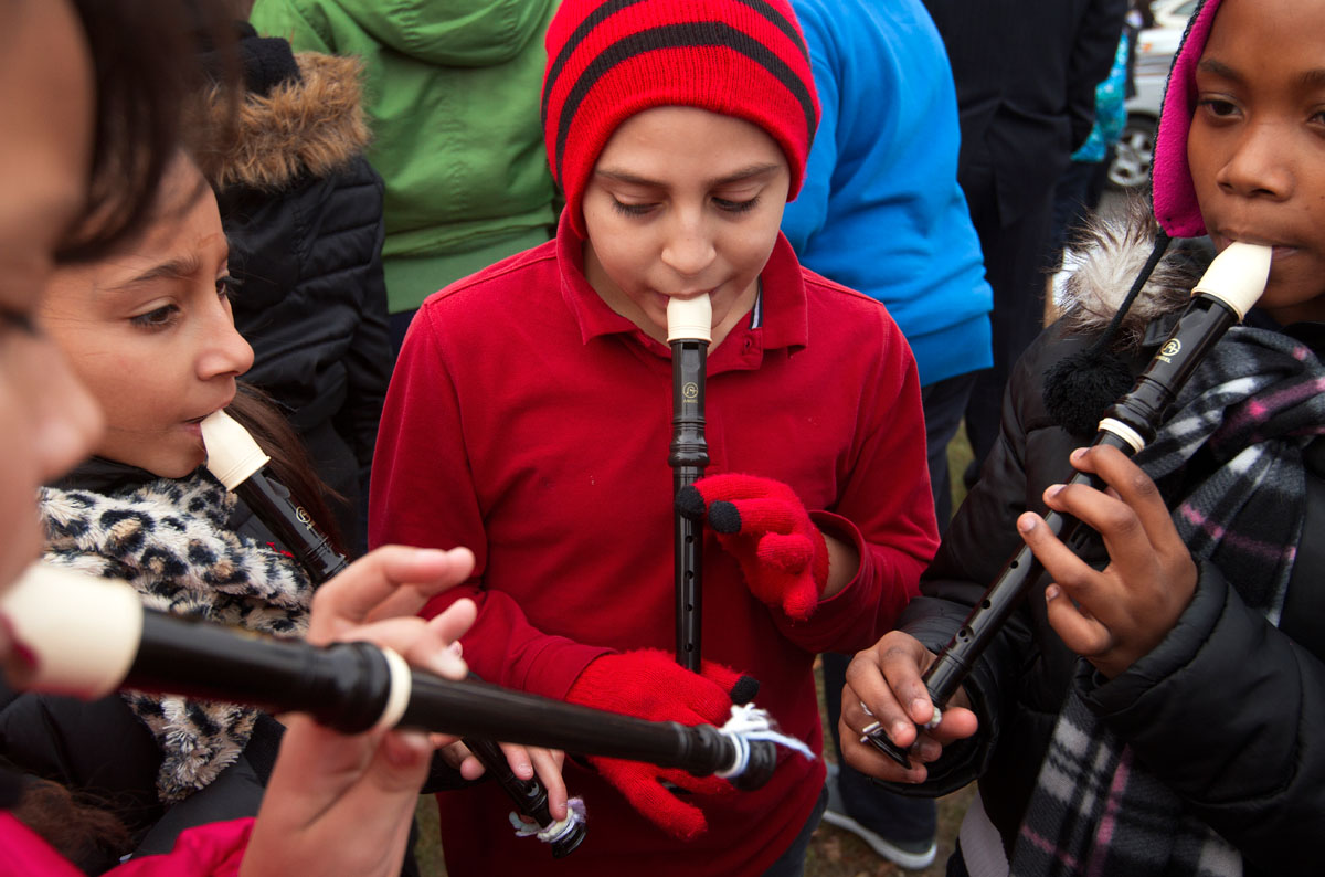 Fifth grader Jose Cruz, center, practices the recorder with classmates from School 20 before the tree lighting ceremony.