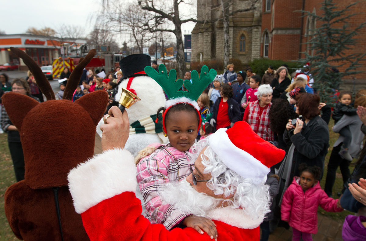Dressed as Santa Claus, Ray Santana from Penfield holds 4-year-old Ariel Hightower during the tree lighting ceremony.