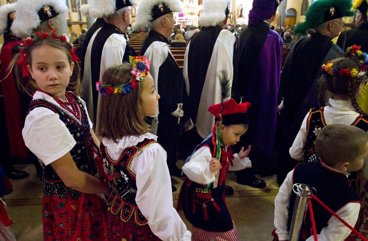 Children dressed in traditional Polish costumes line up next to Knights of Columbus before processing down the aisle at the beginning of Mass at St. Stanislaus Kostka Church in Rochester Dec. 15. As part of the Mass, a stained glass window was dedicated in memory of Tomasz Kaczowka, who was shot and killed while responding to a fire with the West Webster Fire Department on Dec. 24, 2012.