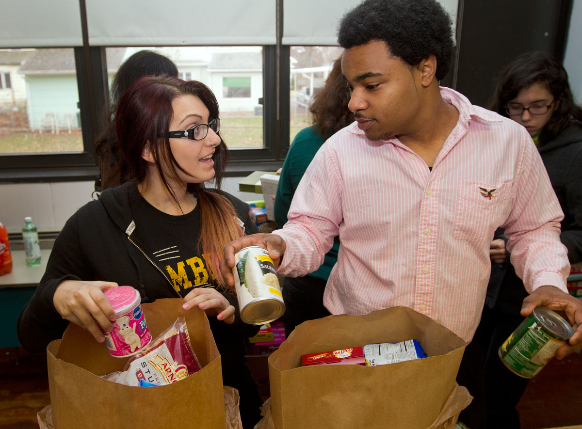 Seventeen-year-olds Toni Peggi, left, and Robert Doleman sort food into bags at St. Charles Borromeo Church in Greece Dec. 8. Parishioners expected to distribute about 75 food bags with items for breakfast, lunch and dinner to families in need before Christmas.