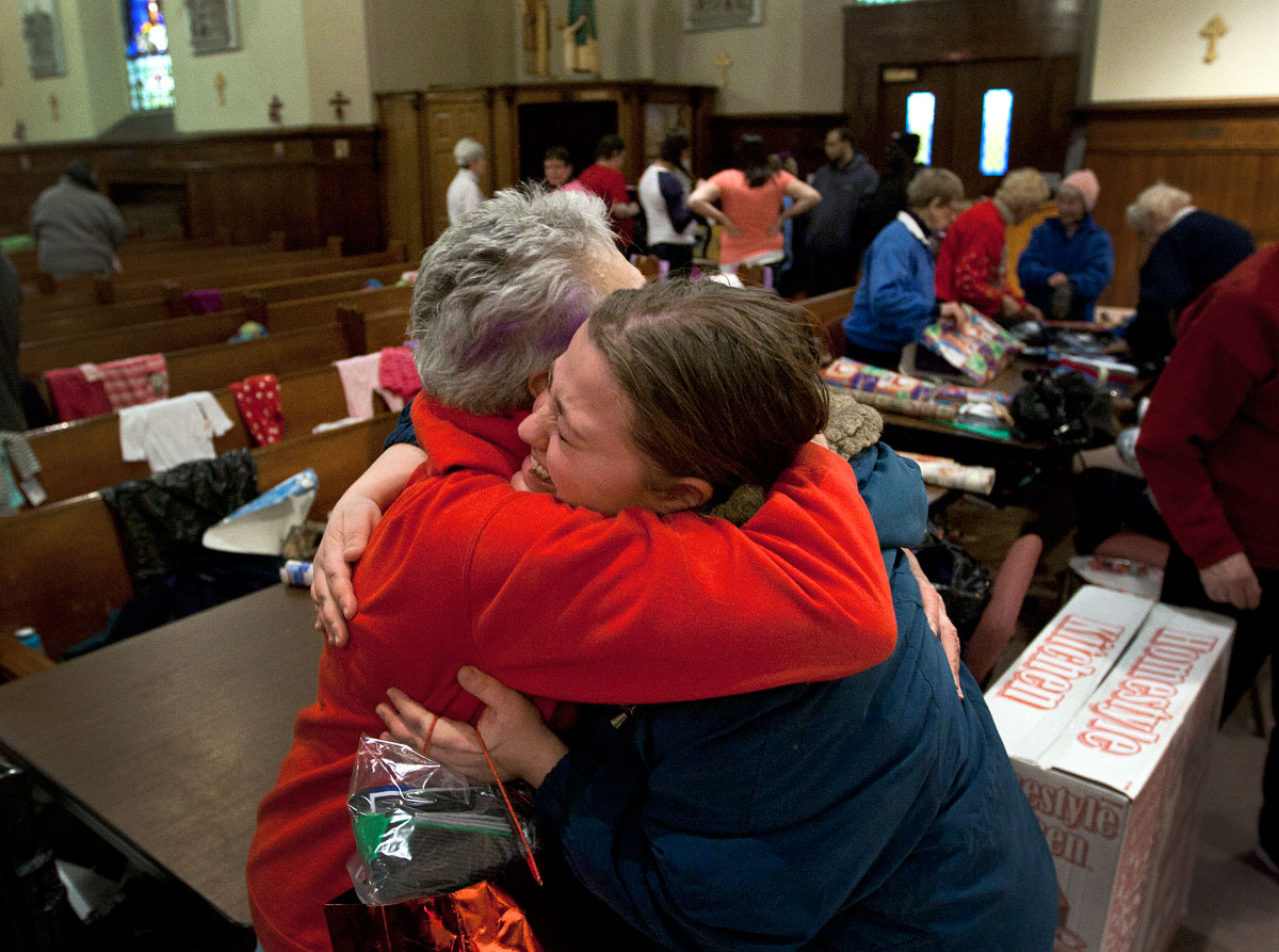 Tina Louk, right, hugs Suzanne Robinson after Robinson helped her to wrap Christmas presents she picked out for her son and other relatives Dec. 19 at Holy Apostles Church in Rochester. Over 80 families in need received gifts and food as part of the parish's Christmas Blessings project.