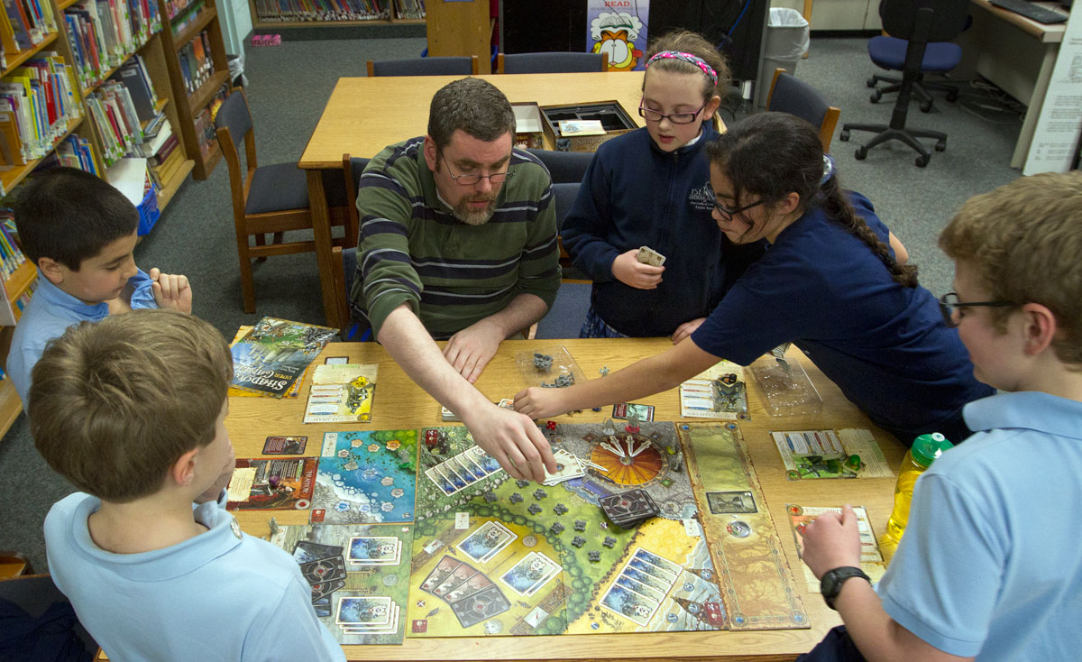 Tom Rued plays Shadows Over Camelot with a group of fifth-graders who are members of the board game club at Seton Catholic School in Brighton. Rued, the school's educational technology coordinator who also works part time at a game store, started the weekly after school club three years ago.