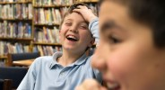 Fifth-grader Charles Laniak laughs at classmate Brenan Hain while setting up the game.