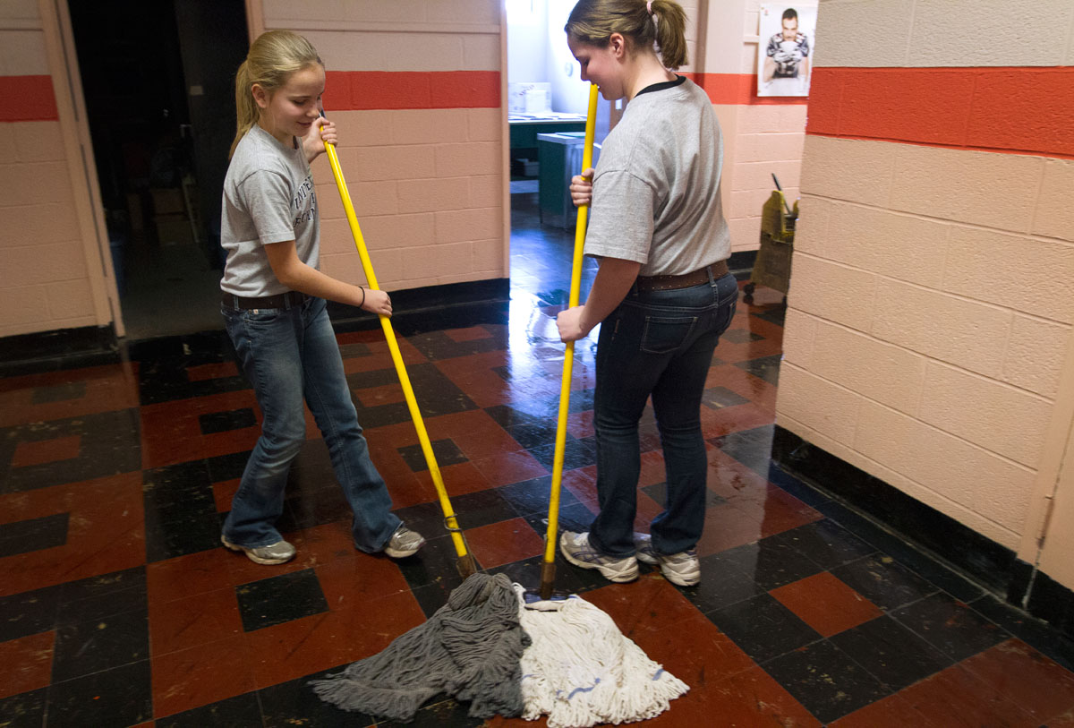 "Samantha Lesch (left) and Alexandra Flurschutz mop a hallway at St. Joseph School in Auburn Jan. 30. The two seventh-graders chose to be custodians on ""In Our Vocations"" day, during which middle school students were able to try out a variety of jobs at the school. The day was part of Catholic Schools Week celebrations."