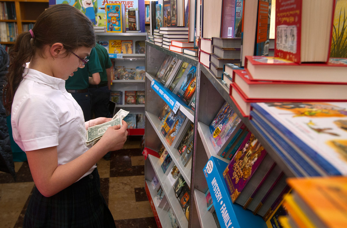 Fifth-grader Liliana Arias counts money while deciding what to purchase from a book fair at St. Joseph School in Auburn Jan. 30.
