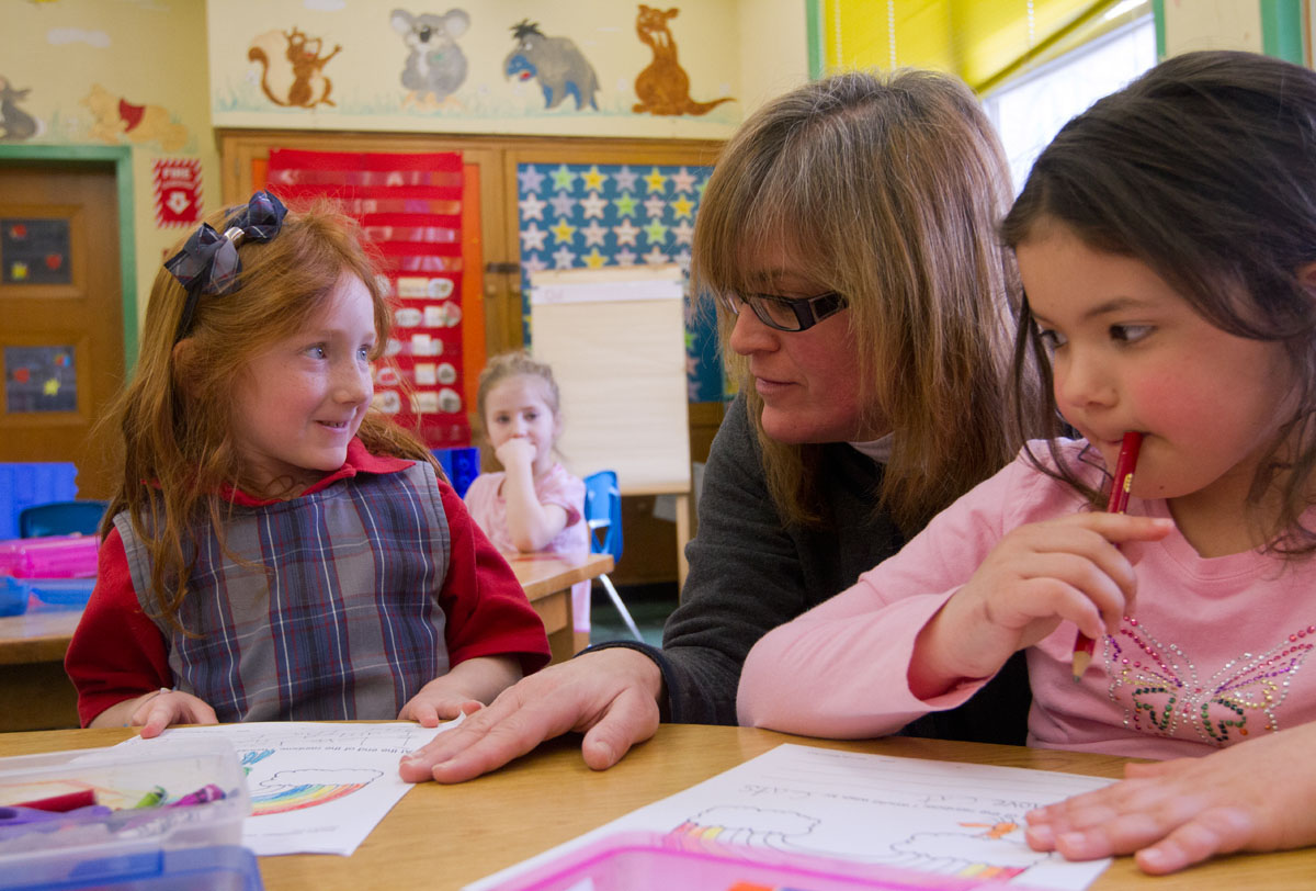 Kindergarten teacher Deborah Sindoni talks with Meghan Forbes (left) and Lauren Godkins March 21 at St. Francis-St. Stephen School in Geneva. Sindoni now teaches in the same classroom in which she was a student.