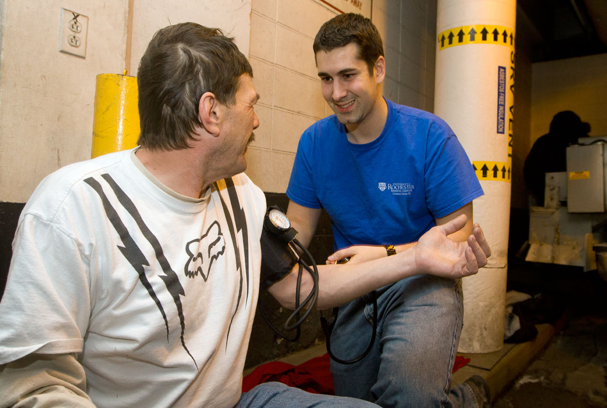 Eric Soriano checks the blood pressure of Kenny Mussaw in the Civic Center Parking Garage in downtown Rochester Feb. 11. Soriano, a medical student at the University of Rochester, participated in outreach to homeless individuals in the garage with other U of R students and volunteers from St. Mary's Church.