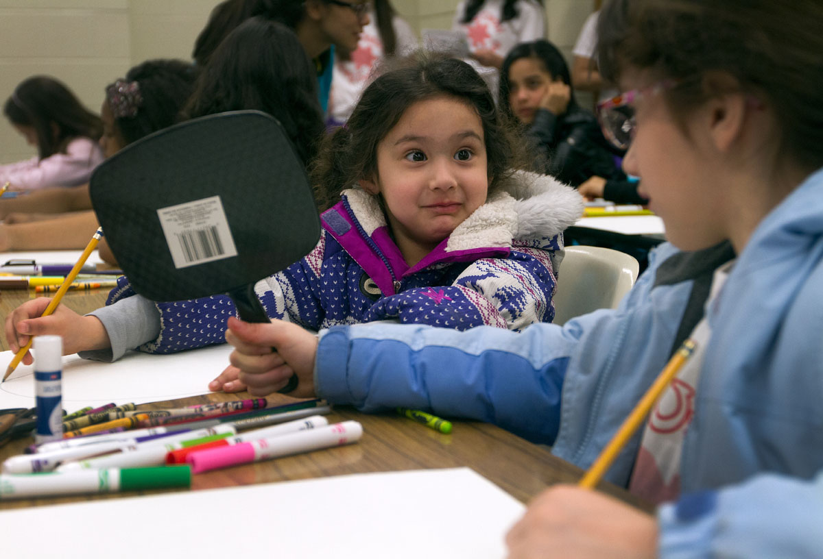 Six-year-old Alejandra Ochoa gets help from her sister, 8-year-old Adriana Ochoa, to use a mirror while creating a self portrait during a student workshop at ÁSoy Unica! ÁSoy Latina! Rally April 19 at Nazareth College.