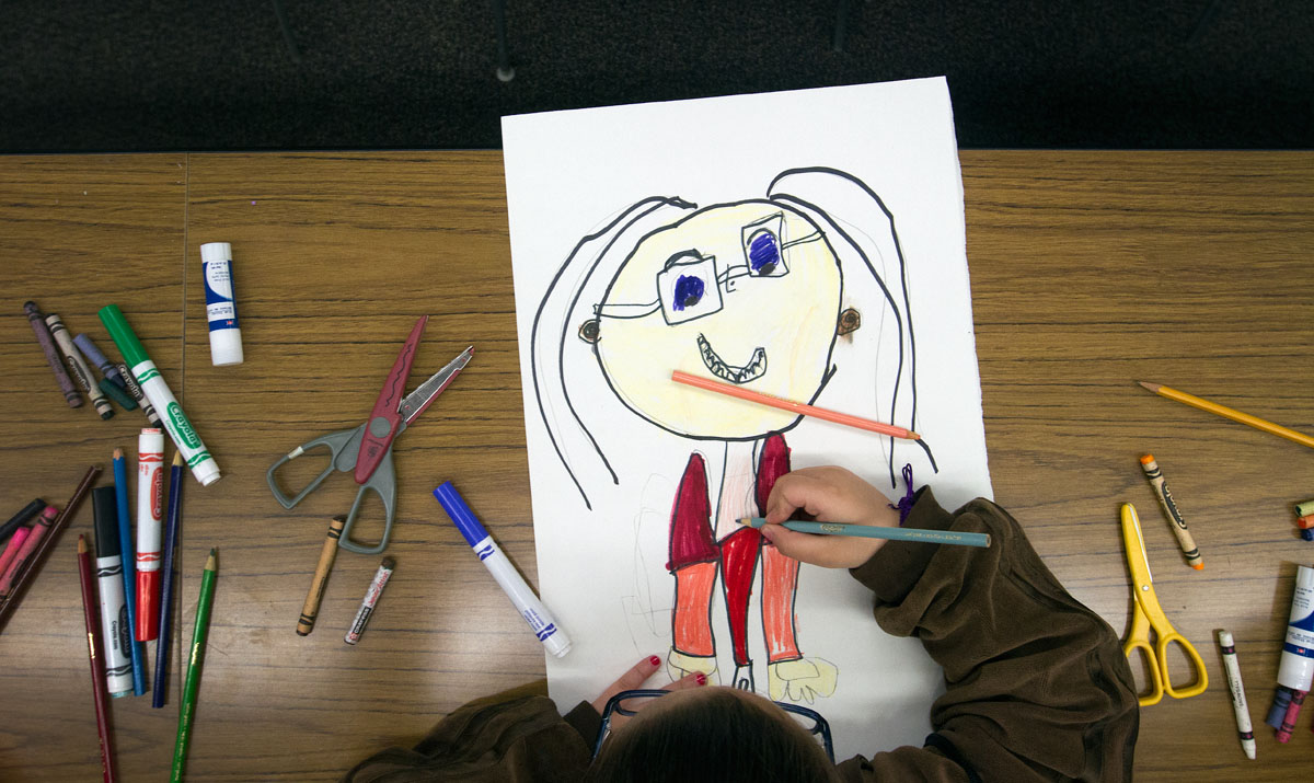 A student draws a self portrait during a student workshop at ÁSoy Unica! ÁSoy Latina! Rally April 19 at Nazareth College.