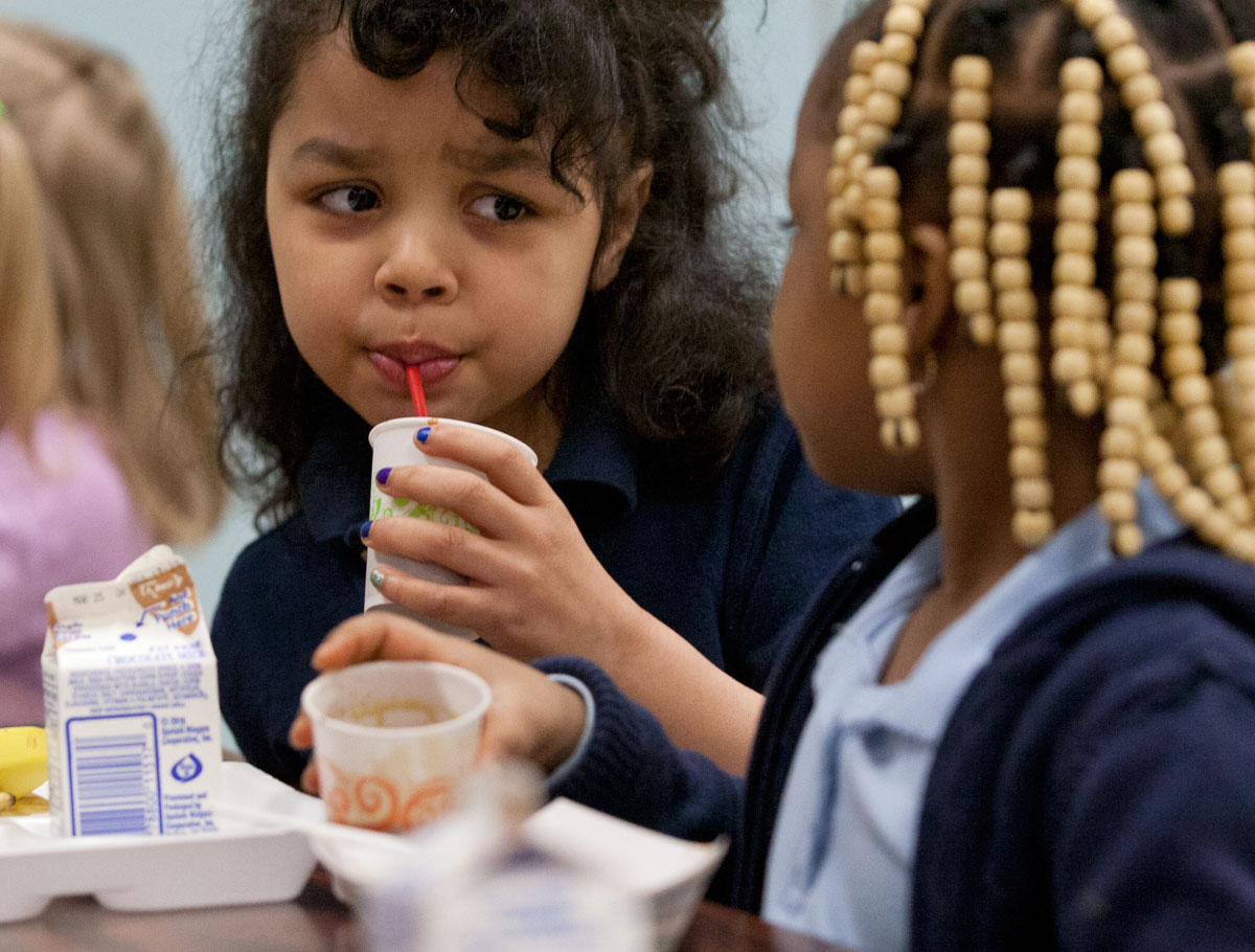 "Kindergartener Gabrielle Mcbride drinks a smoothie while visiting with classmate Nakiyah Calok during lunch at James P.B. Duffy School No. 12 in Rochester March 19. As part of the ""Edible Education"" program, representatives from the Good Food Collective gave students the smoothies, which were made of peaches, spinach, strawberries and blueberries."