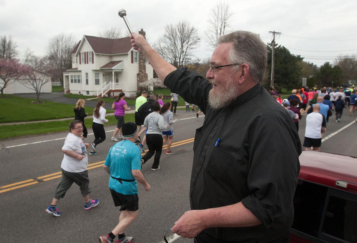 Father Dan Condon, Chancellor of the Diocese of Rochester, blesses runners with holy water as they leave the starting line of the Run for the Young 5k at St. Lawrence Church in Greece May 3.