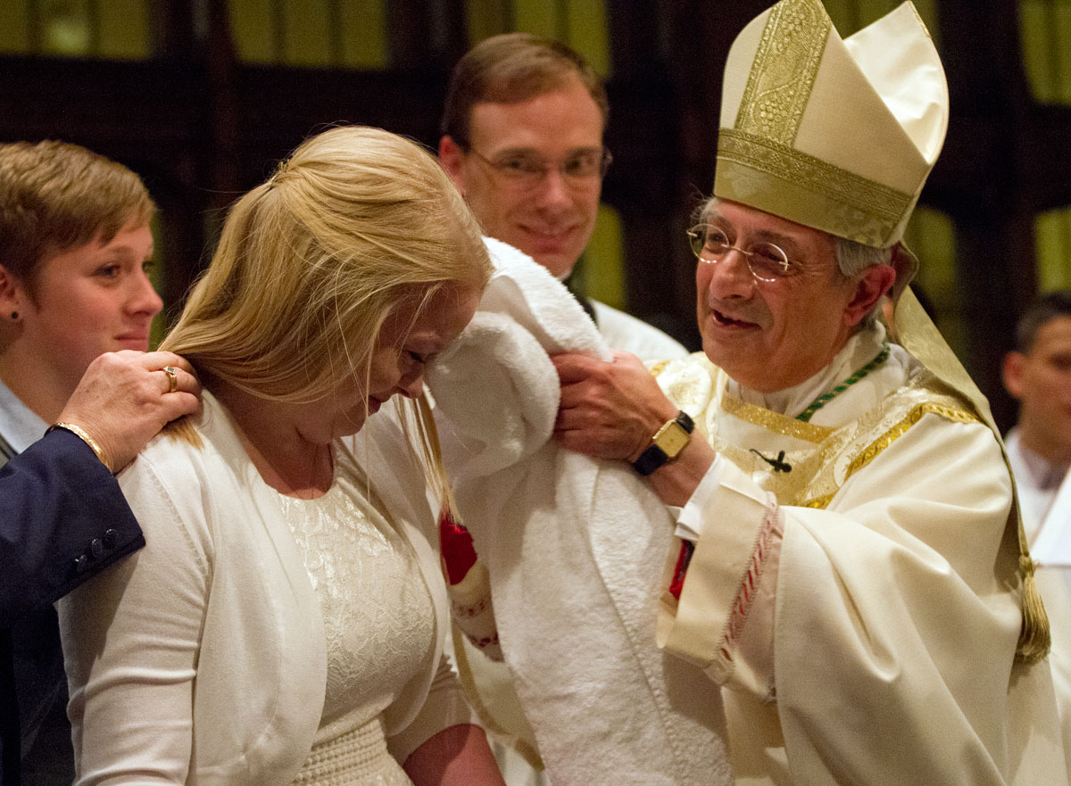 Bishop Salvatore R. Matano dries off Tina Eligon's hair after baptizing her during the Easter Vigil at Sacred Heart Cathedral April 19. Bishop Matano welcomed 13 people into the church while celebrating Mass with the Cathedral Community.