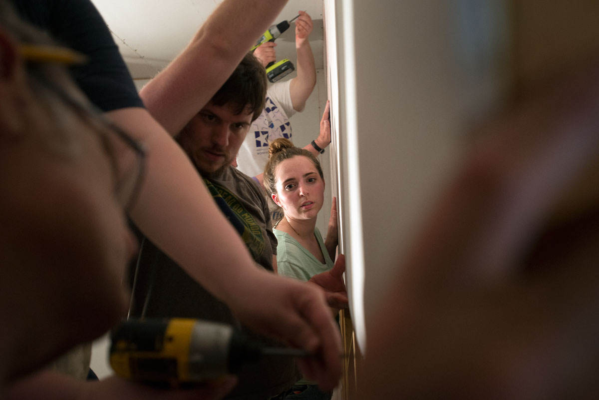 James Pike and Alice Swarthout hold up a piece of Sheetrock while other volunteers attach it to a bedroom wall at a home in Genoa, W.Va. Eighteen volunteers from the Gates Catholic Community traveled to the Appalachians on a mission trip at the end of May.