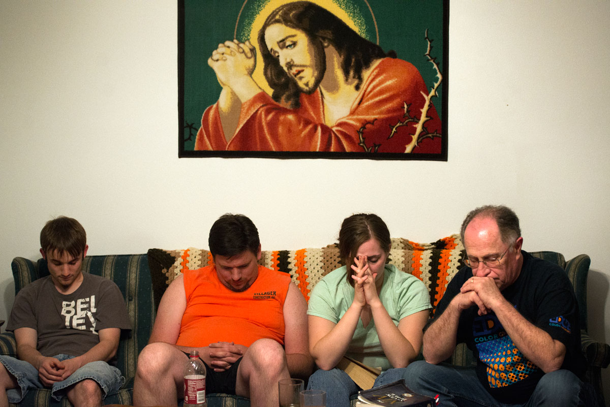 Jonathan Willistein (from left), James Pike, Alice Swarthout and Jim Stocks pray at the end of a Bible study May 20 at the house they stayed at in Louisa, Ky.