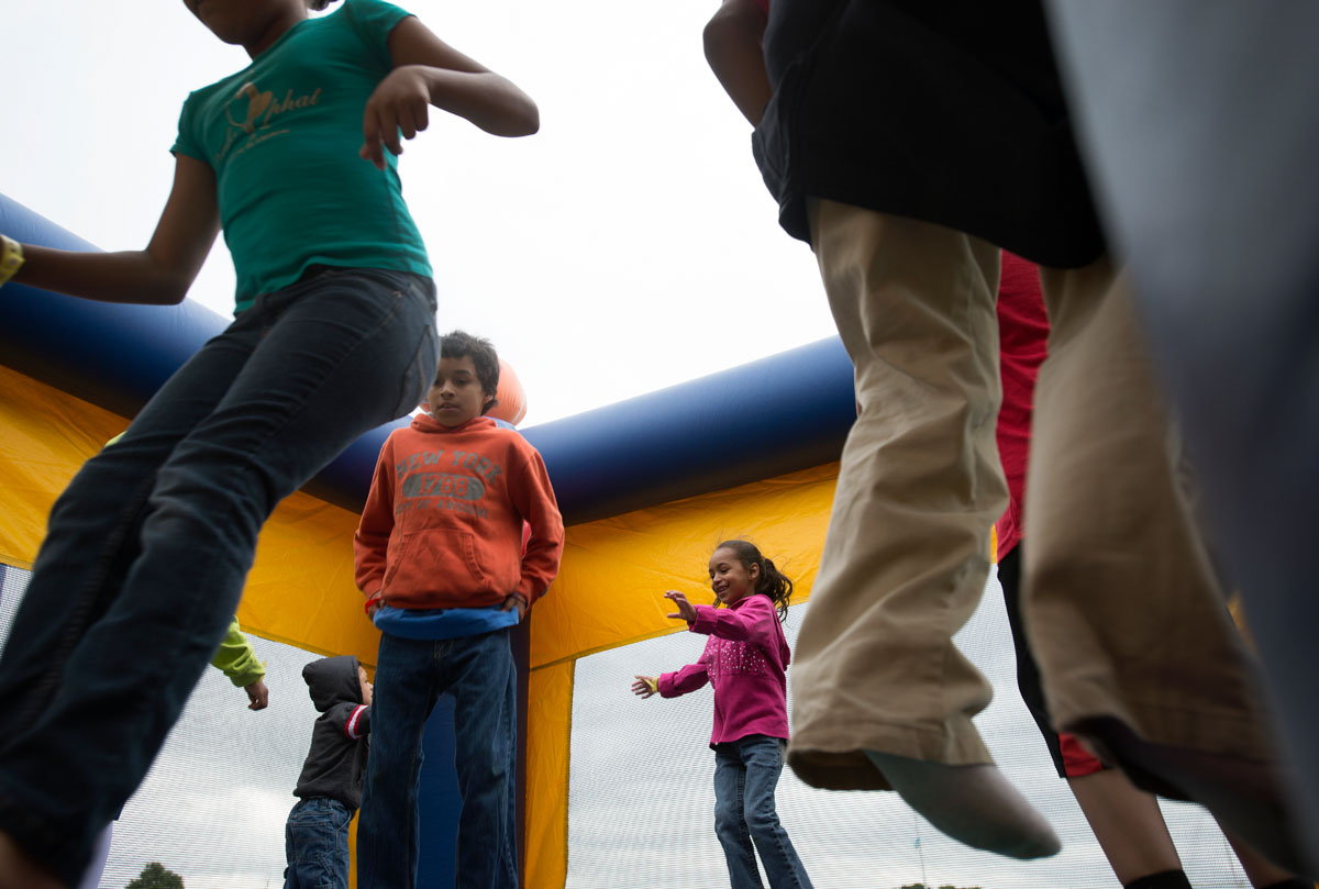 Nine-year-old Lyan Ortiz (from left), 8-year-old Reinaldo Sepulveda and 5-year-old Rihanna Sepulveda jump in a bounce house during the Rochester City School District Latino Family Fair June 14 at Rochester International Academy.