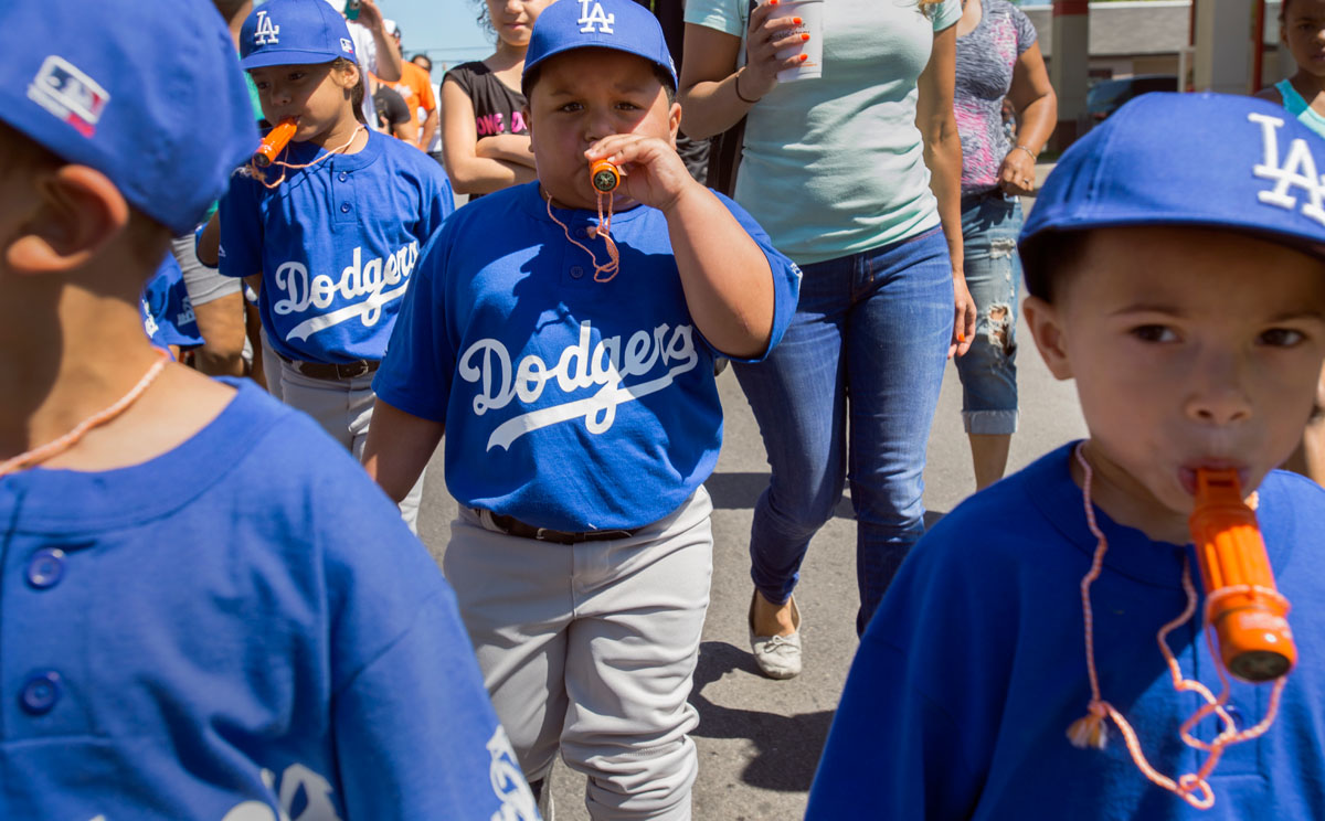 Five-year-old Luis Manuel Ramos blows a whistle while walking with teammates in a parade down Clinton Avenue to kick off the Rochester Hispanic Youth Baseball League's 19th season June 7.